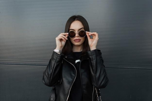 Elegante ritratto urbano di una ragazza hipster alla moda con una giacca di pelle nera e felpa raddrizza occhiali da sole vintage sullo sfondo di un muro di metallo in città