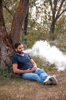 Elegante uomo di vape che vaping un dispositivo di fumo elettronico