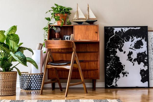 Design degli interni elegante e vintage del soggiorno con comò retrò in legno, sedia, piante tropicali, navi e accessori eleganti.