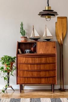 Interior design elegante e vintage del soggiorno con comò retrò in legno, piante, navi, pagaia, mappa.