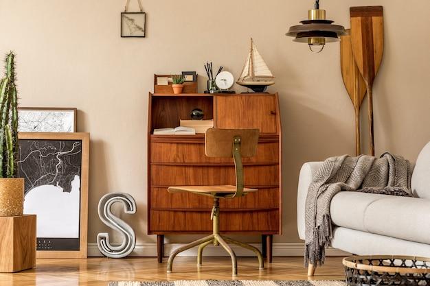 Design d'interni elegante e vintage di open space con armadio retrò in legno, sedia di design, divano, pagaia, nave, cactus, piante ed eleganti accessori personali. modello. arredamento moderno per la casa d'epoca.