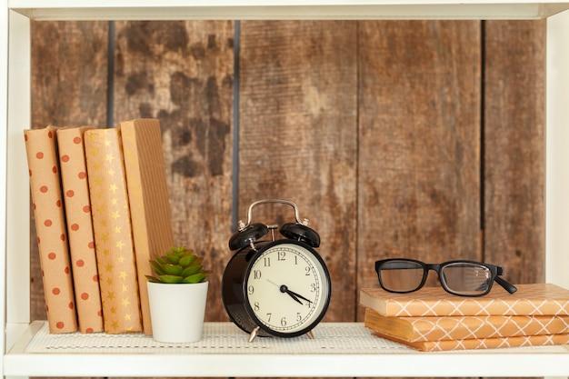 Scaffale per libri bianco alla moda contro la parete di legno del grunge