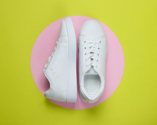 Eleganti sneakers bianche su carta verde con cerchio rosa pastello