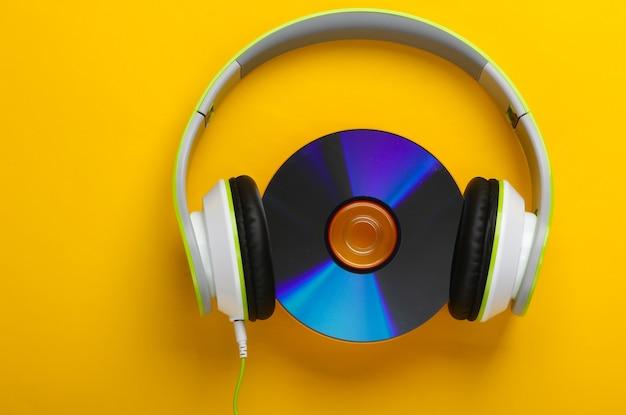 Cuffie stereo cablate alla moda con disco cd su superficie gialla