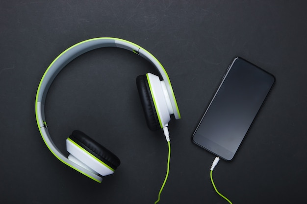 Eleganti cuffie stereo cablate con smartphone su superficie nera