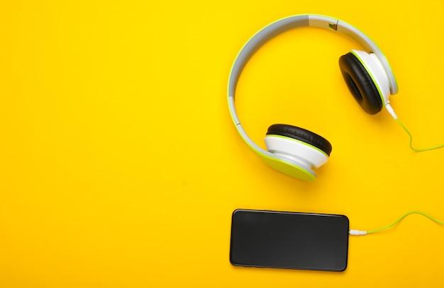 Eleganti cuffie stereo cablate con smartphone sulla superficie gialla Foto Premium