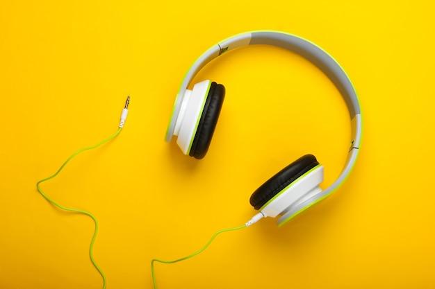Cuffie stereo cablate alla moda sulla superficie gialla