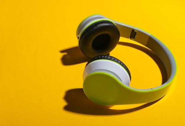 Cuffie stereo senza fili alla moda con ombra sulla superficie gialla