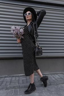 Elegante donna in abiti neri alla moda in cappello vintage in occhiali da sole alla moda con borsa con bouquet di fiori lilla freschi si trova vicino al muro di metallo grigio in strada. bella ragazza in abito nero primaverile.
