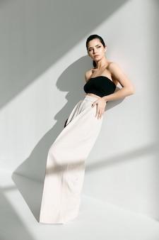 Donna alla moda in vestiti alla moda che si appoggia contro la parete all'interno