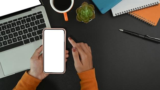 Mani di donna alla moda utilizzando smart phone nell'area di lavoro moderna.