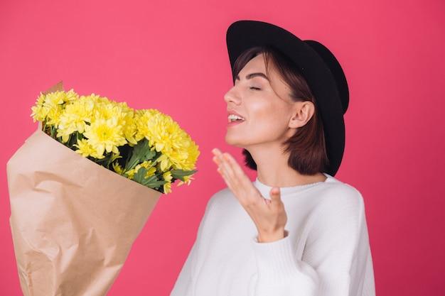 Donna alla moda in cappello sulla parete rossa