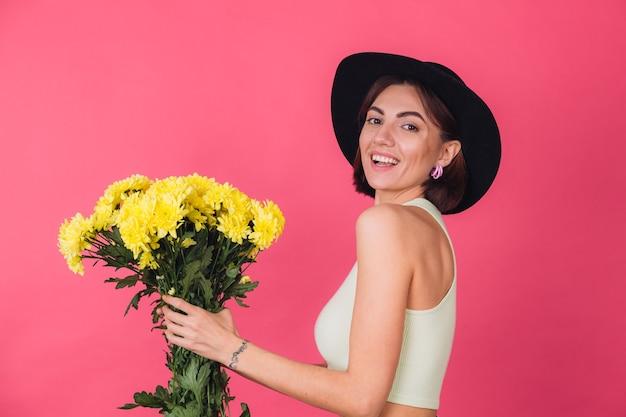 Donna alla moda in cappello, sorseggia a sinistra grande mazzo di astri gialli, umore primaverile, spazio isolato di emozioni felici