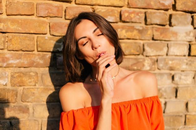 Donna alla moda in vestiti arancioni al tramonto al muro di mattoni che fuma sigaretta elettronica