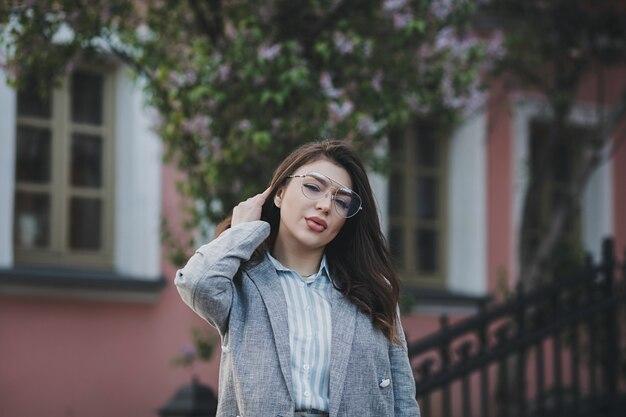 Donna alla moda in posa per strada alla città vecchia, indossa giacca e occhiali, donna glamour di affari