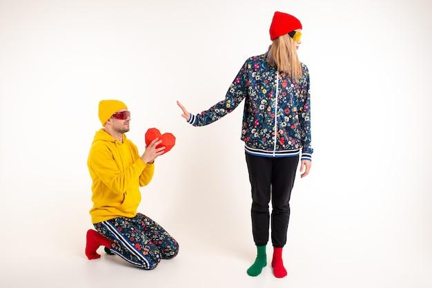 Donna alla moda che rifiuta un cuore di donazione dal ragazzo in abiti colorati su sfondo bianco