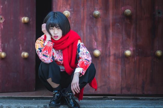 Donna alla moda accovacciata davanti alla tradizionale porta di legno