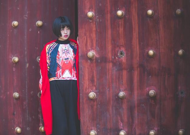 Donna alla moda in piedi davanti alla tradizionale porta di legno