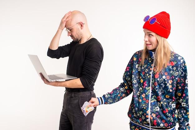 Donna alla moda che ruba soldi dall'uomo che lavora al computer sopra priorità bassa bianca