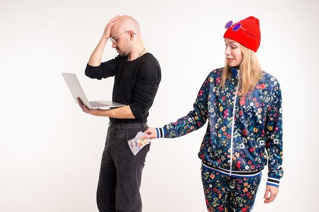 Donna alla moda che ruba soldi dall'uomo che lavora al computer sopra il muro bianco