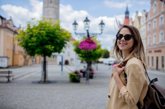 Donna alla moda in occhiali da sole e zaino in piazza del centro città invecchiata