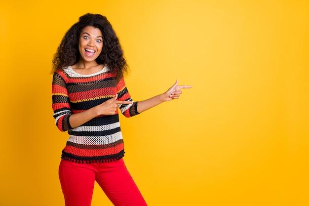 Donna alla moda con acconciatura afro in posa contro il muro arancione