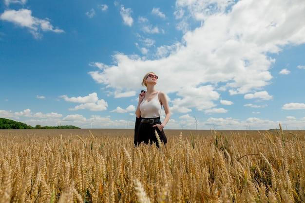 Donna alla moda con capelli biondi che posano in vestiti convenzionali nel campo di grano wheat
