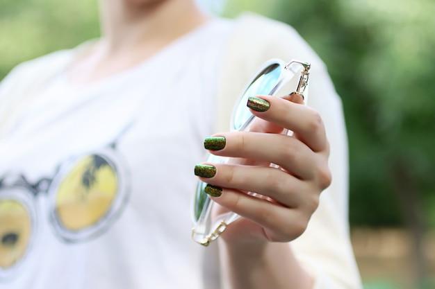 Donna alla moda con unghie luminose che tengono gli occhiali in mano. tecnica di nail art glitterata. idea per manicure.