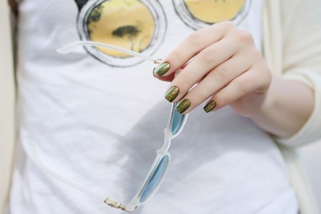 Donna alla moda con unghie luminose che tengono gli occhiali in manotecnica di nail art glitterata