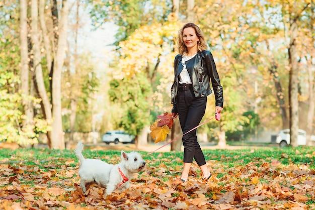 Donna alla moda con il cane su una passeggiata nel parco di autunno. stile di vita, moda e concetto di umore autunnale.