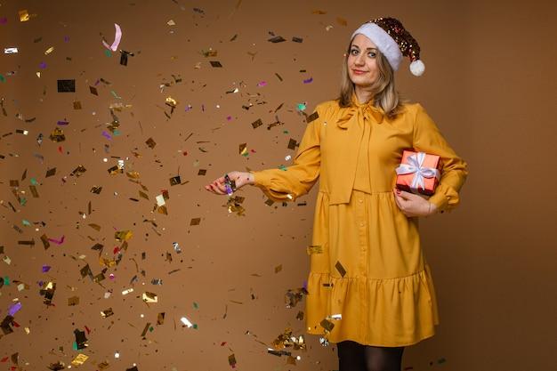 Elegante donna in abito giallo, scarpe nere e cappello rosso di natale tiene una scatola rossa con un regalo con un sacco di confettin intorno a lei