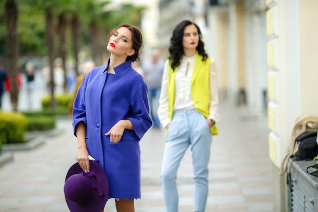 Le donne alla moda modellano tra i 20 ei 25 anni in una piazza di una città europea