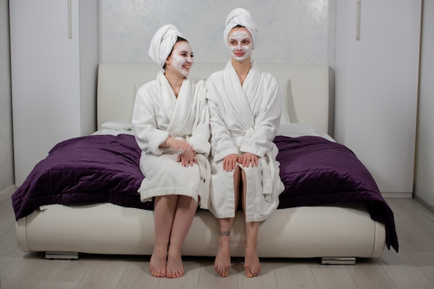 Donne alla moda in accappatoi, asciugamani in testa e maschera sul viso si siedono sul letto in camera da letto e sorridono foto di alta qualità
