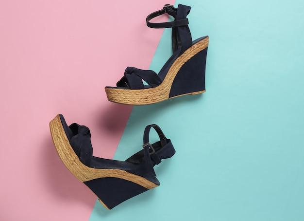 Sandali da donna alla moda sulla piattaforma su carta pastello rosa blu