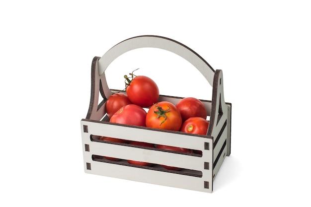 Elegante scatola di legno con pomodori isolati su sfondo bianco.
