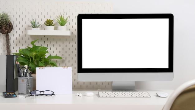 Elegante computer bianco sul posto di lavoro, piante d'appartamento e forniture sul tavolo bianco.