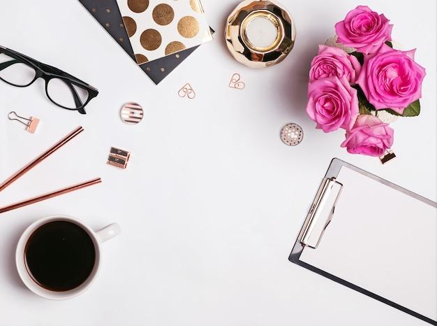 Posto di lavoro elegante con caffè, rose rosa e accessori eleganti su sfondo bianco