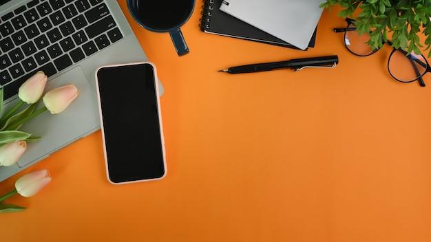 Elegante area di lavoro con smartphone, laptop, notebook, occhiali e fiori su sfondo arancione.