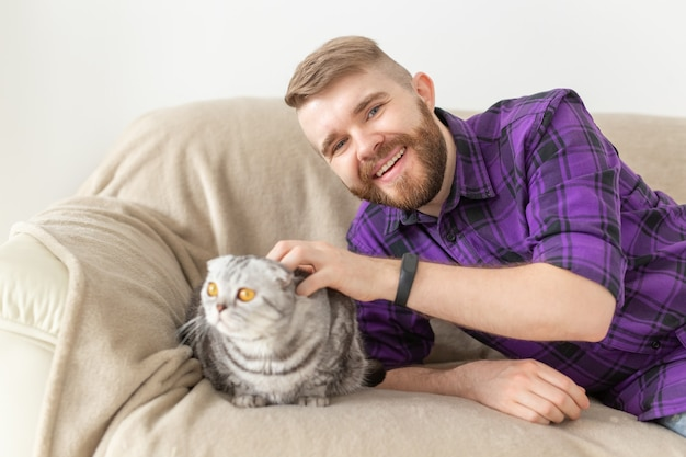 Elegante giovane uomo barbuto hipster accarezzando il suo bellissimo gatto grigio scottish fold seduto sul divano. concetto di cura degli animali.