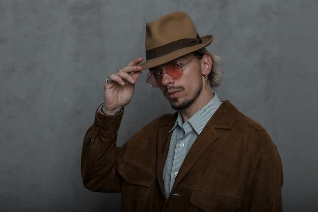 Elegante giovane barbuto in occhiali rotondi rosa in un cappello elegante in una giacca marrone alla moda in una camicia classica in posa vicino a un muro grigio in studio. modello di ragazzo attraente. stile retrò.
