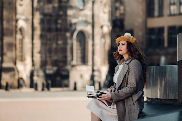 Una giovane bella ragazza alla moda è seduta e sta digitando nella città vecchia di dresden.germany.