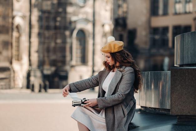 Una giovane bella ragazza alla moda è seduta e sta digitando nella città vecchia di dresda
