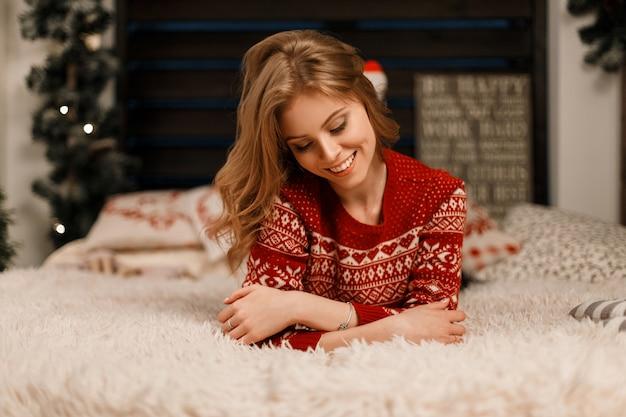 Elegante giovane bella donna in un maglione vintage alla moda con un ornamento appoggiato sul letto