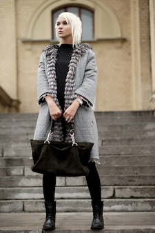 Elegante giovane donna bionda che indossa un look invernale
