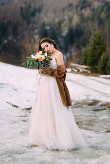 Elegante giovane sposa con un mazzo di fiori gode di una bella giornata.