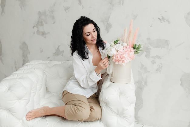 Elegante giovane ragazza bruna con i piedi nudi in pantaloni beige e una camicia bianca e un mazzo di fiori si siede su una poltrona bianca