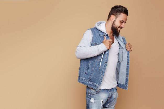 Elegante giovane ragazzo allegro con una bella barba in una giacca di jeans e t-shirt bianca su un semplice sfondo color crema