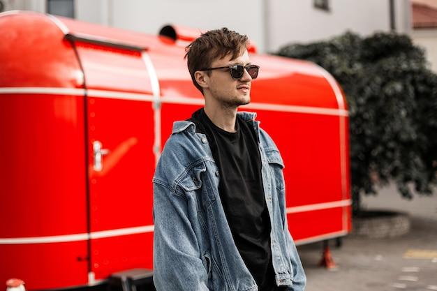 Uomo alla moda giovane hipster cool in una giacca di jeans in una maglietta nera in occhiali da sole con un'acconciatura in posa vicino a un furgone rosso metallo vintage. il modello di ragazzo alla moda americano sta riposando in città. stile di strada.