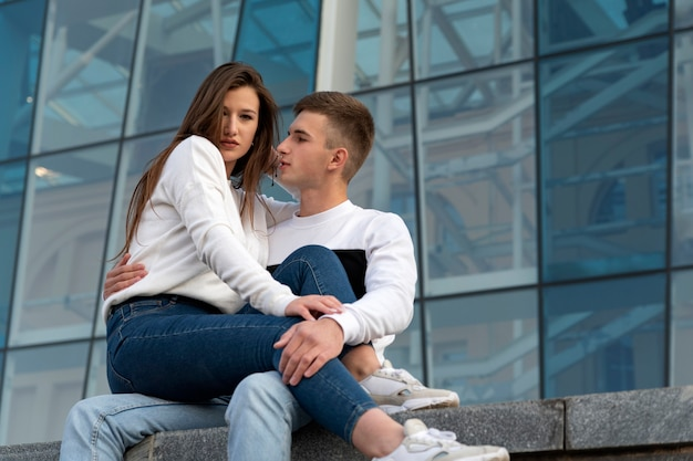 Elegante giovane coppia sullo sfondo della facciata in vetro dell'edificio. la ragazza è seduta sulle ginocchia del ragazzo. amore studentesco.