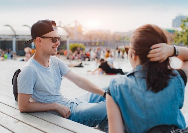 Elegante giovane coppia divertirsi chiacchierando tramonto estivo piazza della città.